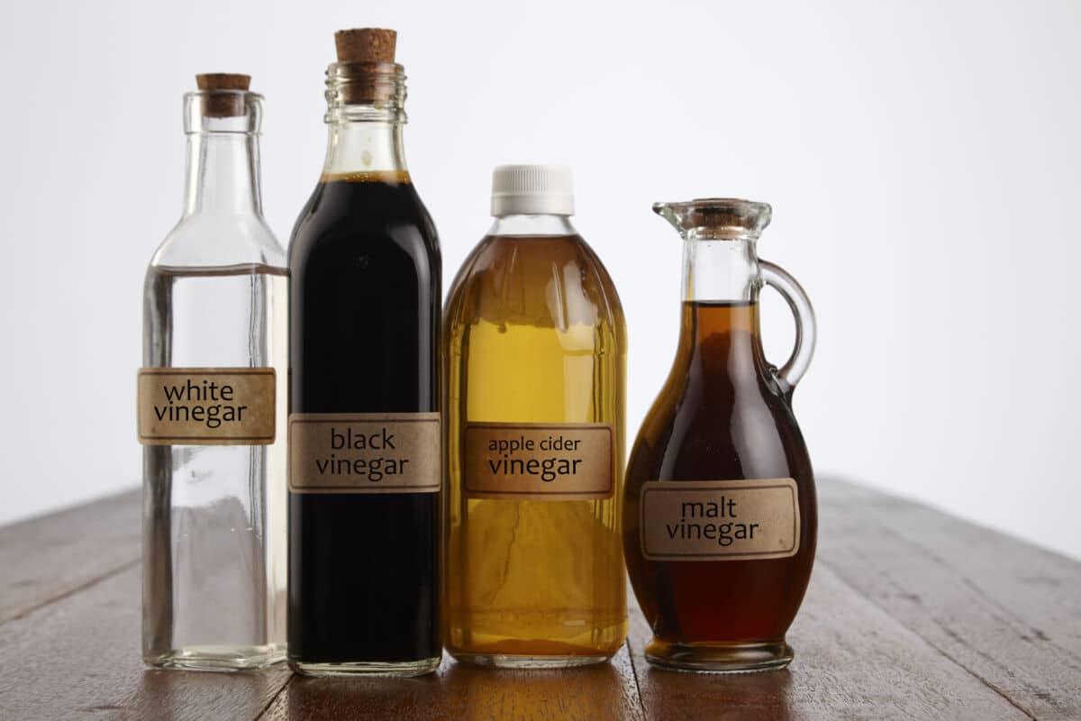 Various bottles of vinegar on a wooden table