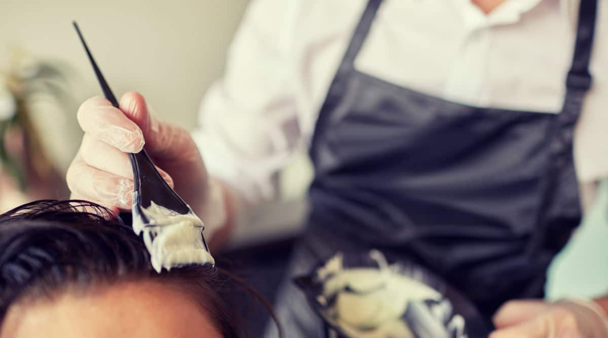Hair dye being applied to a brunette, by a person in a blue apron