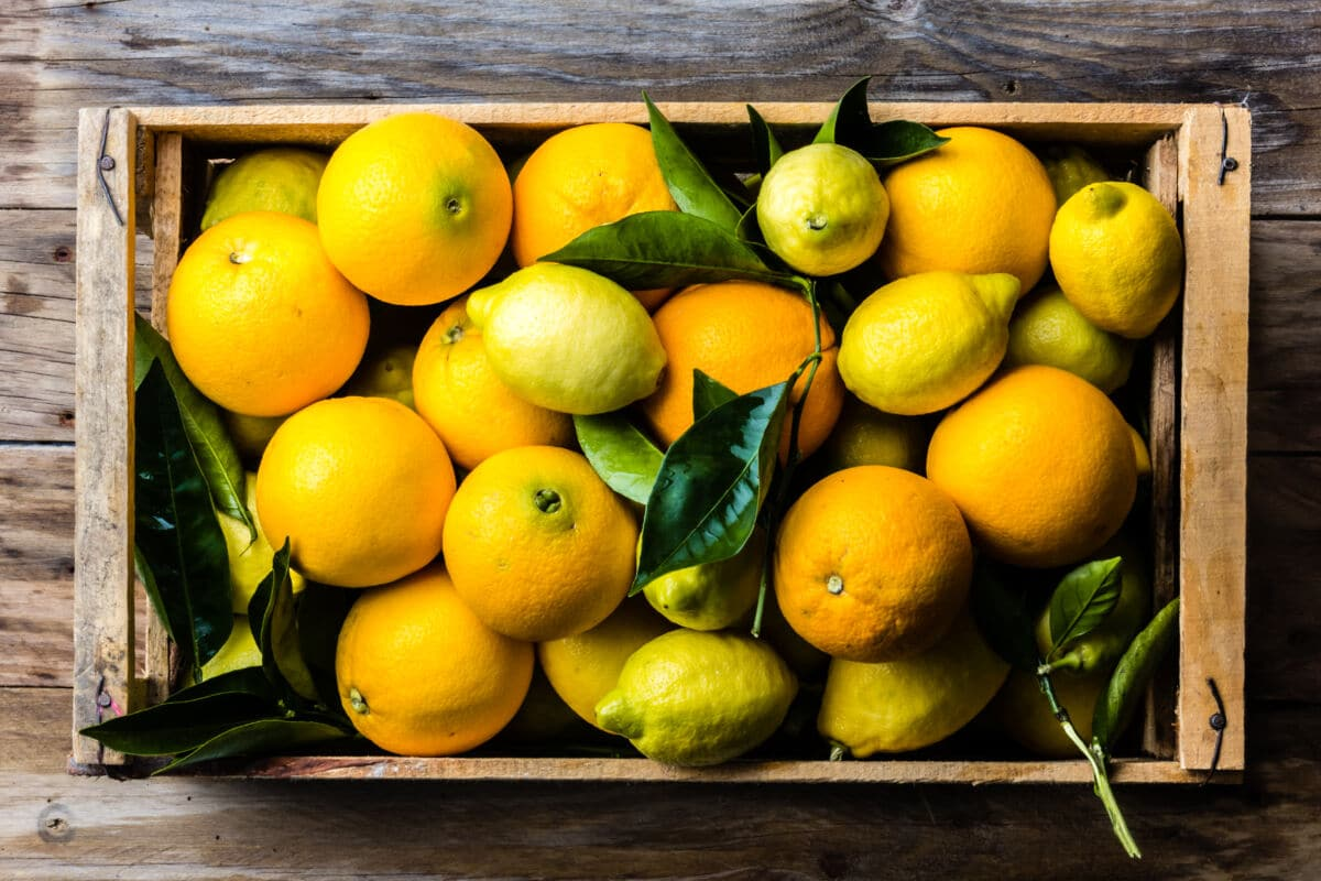 A wooden tray full of lemons and oranges, some with leaves still attached