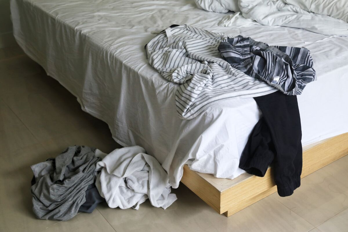 messy clothes on a bed