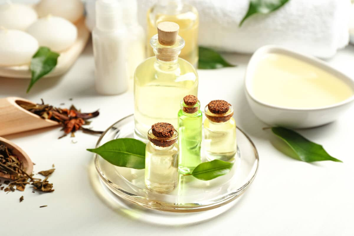 Different sized bottles of tea tree oil on a plate, with a few tea tree leaves