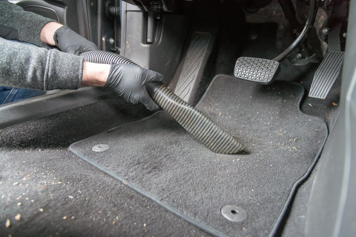Gloved hands vacuuming the floor of a car, with a few food crumbs visible